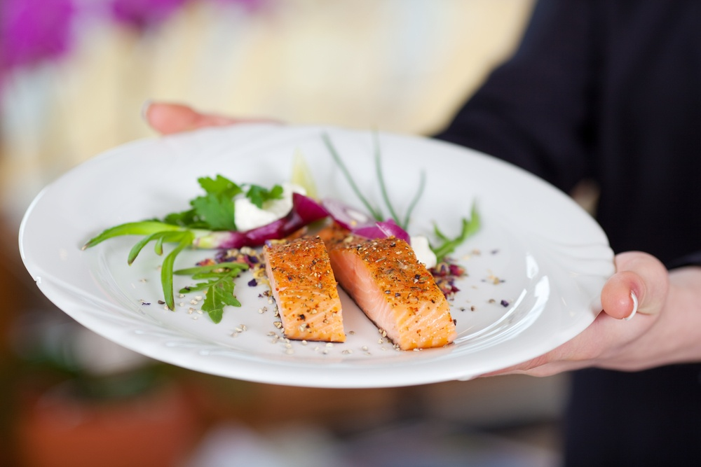 Cropped image of waitress displaying salmon dish in restaurant-1