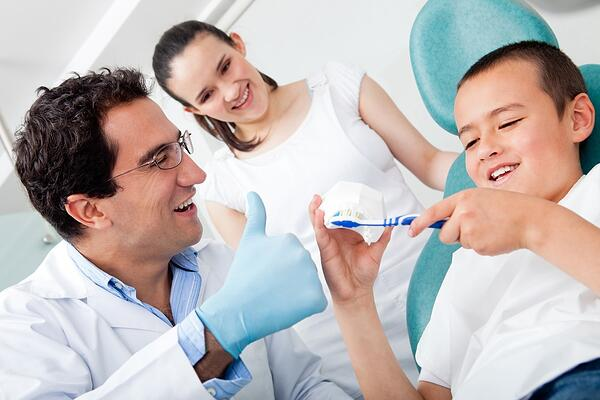 Dentist showing a boy how to brush his teeth properly