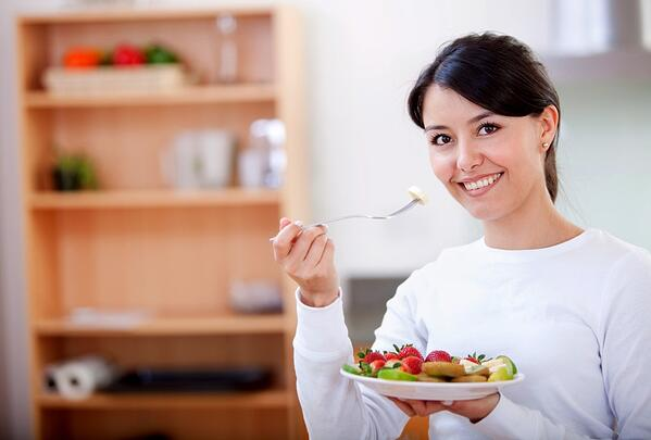 Healthy eating woman with fruit salad smiling